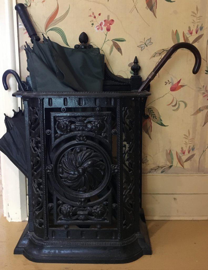 Photo d'un porte-parapluie en fonte peint en noir d'une hauteur d'environ deux pieds et demie (environ 62 cm), d'une largeur de 18 pouces (environ 45 cm) et d'une profondeur d'environ six pouces (environ 15 cm). L'armature en fonte est ornée de motifs floraux symétriques. On aperçoit les poignées recourbées de deux parapluies et une ombrelle dépassant le haut du support adossé à un mur couvert de papier peint fleuri.