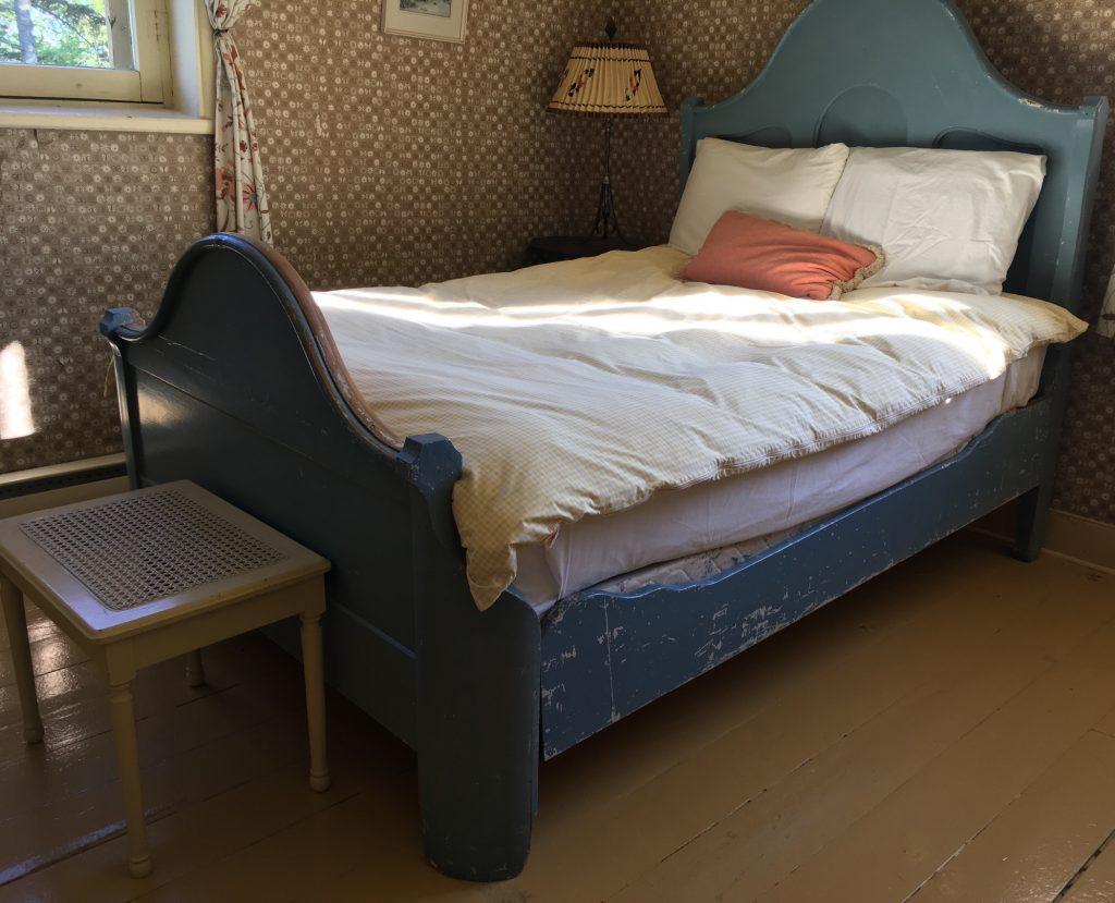 Photographie couleur d'un lit antique, le lit de Sir John A., en bois trois quarts, à tête haute et à pied plus bas, dont la peinture de couleur bleue est écaillée de façon marquée sur son côté.