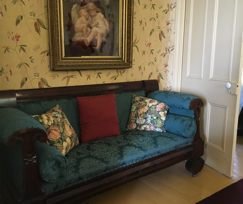 A colour photo of an old-fashioned upholstered chesterfield set in a nook behind a door, its back against a wallpapered wall upon which hangs a painting of cherubs.