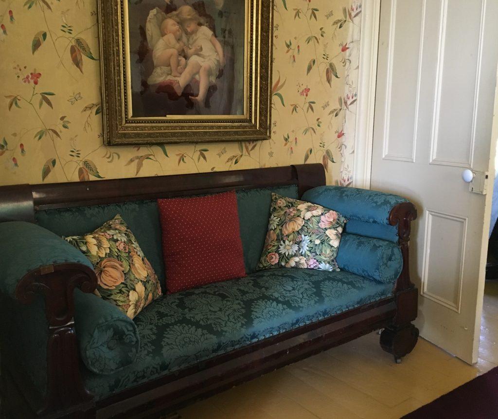 Une photo couleur d'un vieux sofa Chesterfield capitonné installé dans le coin d'une pièce derrière une porte, le dos contre un mur recouvert de papier peint sur lequel est accroché un tableau illustrant des chérubins.