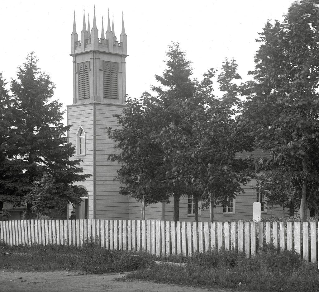 Black and white photo of an old wooden church, St. Bartholomew's Anglican church with a steeple in front, one person emerging from the front entrance, and a picket fence all across the front of the church property, in the foreground of the photo. Also there are several large trees between the fence and the church.