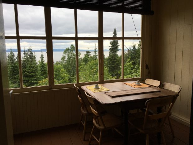 A colour photo of a small room featuring three sets of quarter-paned windows that reveal woods, river, and sky. Inside the small room, on the viewer's side of the windows, is a small wooden table with five wooden chairs and breakfast places set for two people.