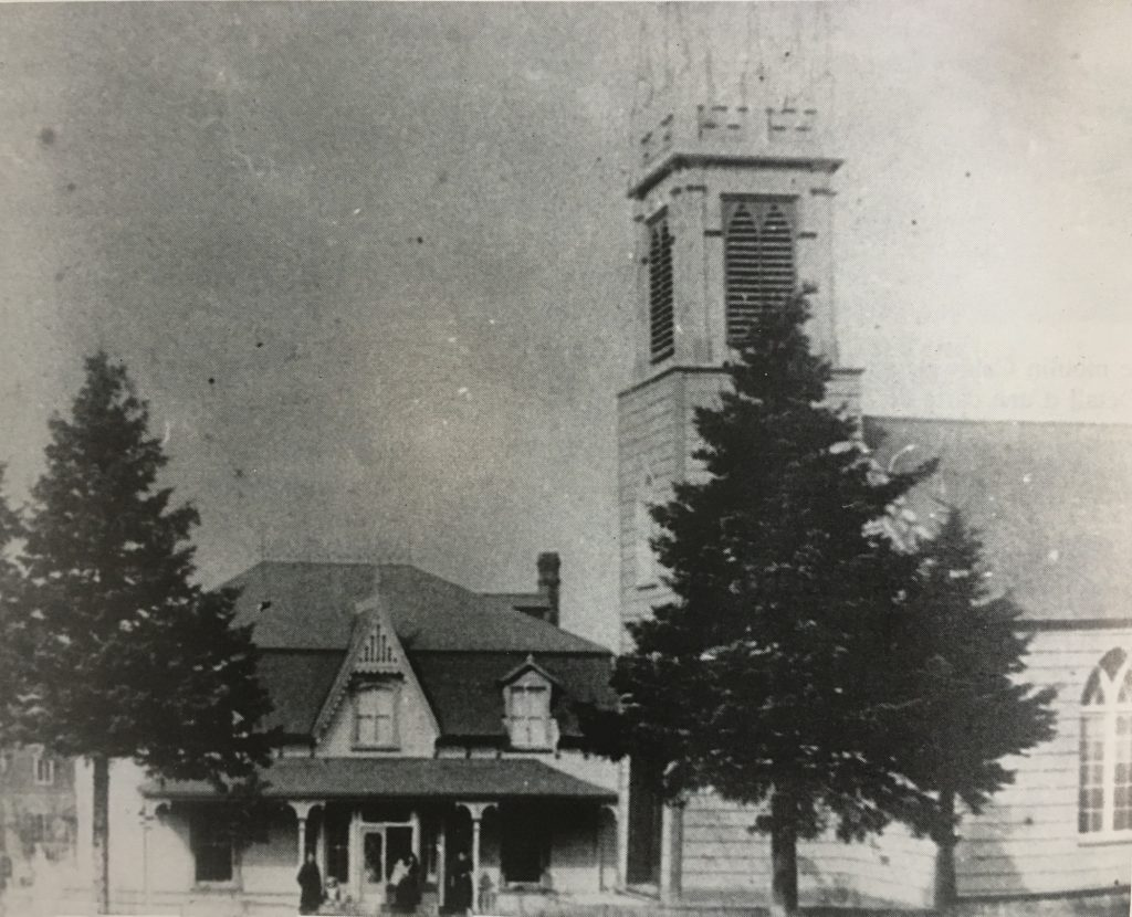A black and white photograph of an old wooden church with a steeple at the front, and a two-storey minister's house erected quite close to the front of the church.