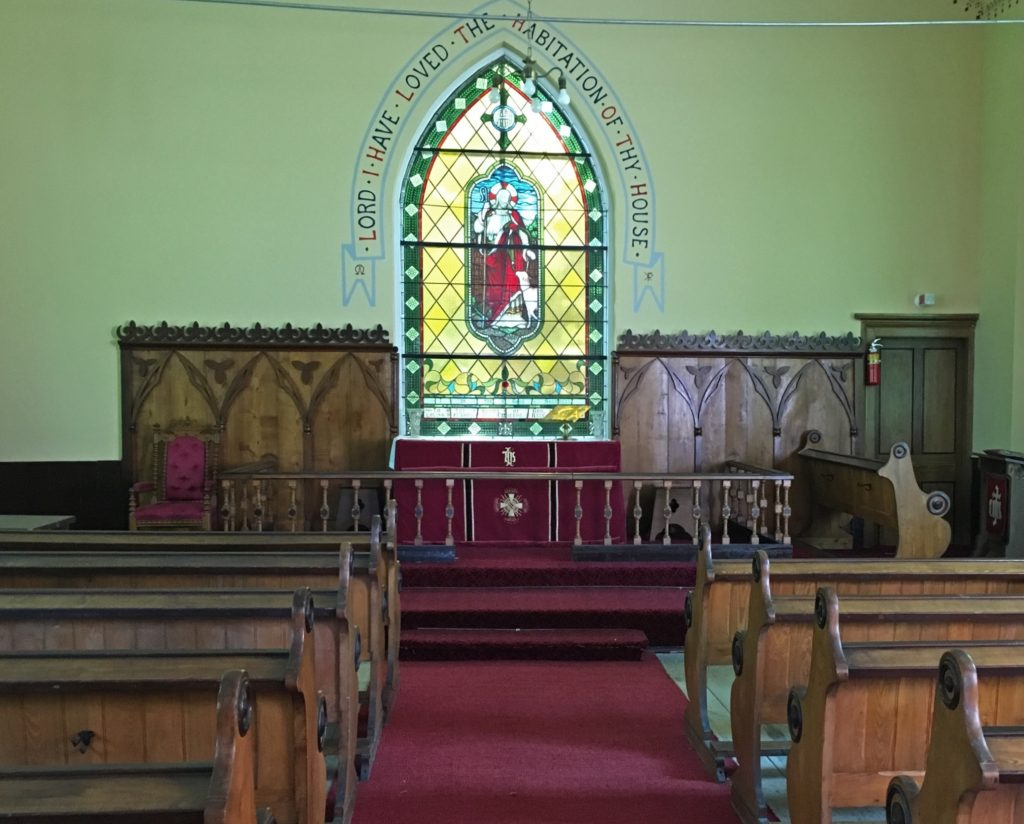 Colour photograph of St. Bartholomew's Anglican church interior, wooden pews, wooden backdrop to altar, a plain wall in the centre of which is a stained glass window.