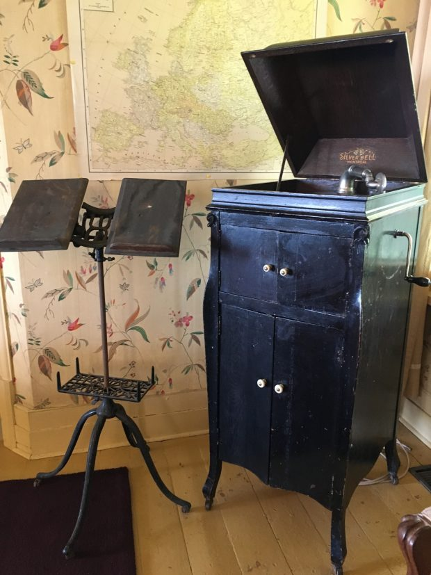 A colour photo of an old wooden victrola, its lid propped open, and next to the victrola is a cast-iron music stand.