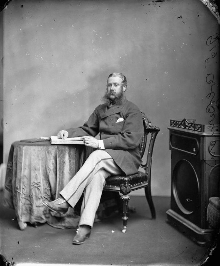 Portrait noir et blanc de Sir Hewitt Bernard assis, vêtu d'un manteau court en laine et d'un pantalon à rayures, les jambes croisées, son bras droit appuyé sur un livre ouvert déposé sur une table ronde.