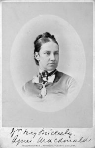 A head-and-shoulders portrait of Lady Agnes Macdonald, a young woman of about 30 to 35 years old, her dark hair pulled tightly into an arrangement of braids pinned behind her head. She wears a buttoned-up shirt, a cameo at her throat and a necklace the details of which are indistinguishable. Her expression is a mixture of thoughtful and stern.