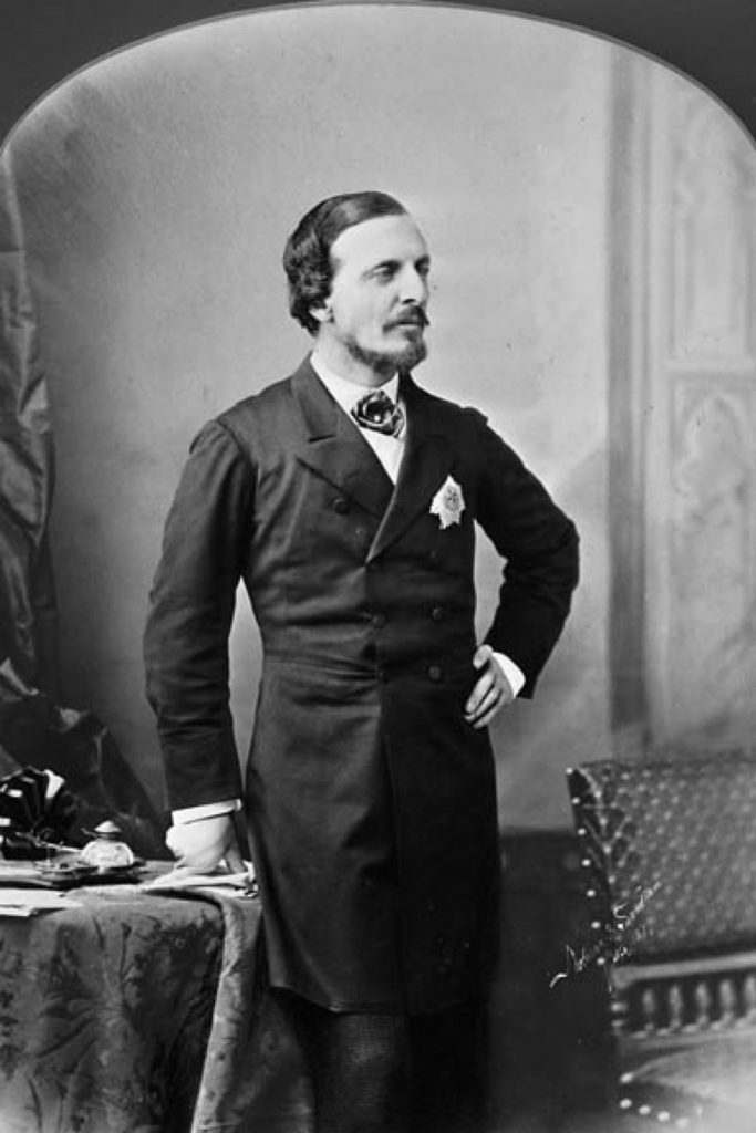 A formal black and white portrait of Lord Dufferin in a dark suite with a white handkerchief in the front pocket, standing with his left hand on his hip.
