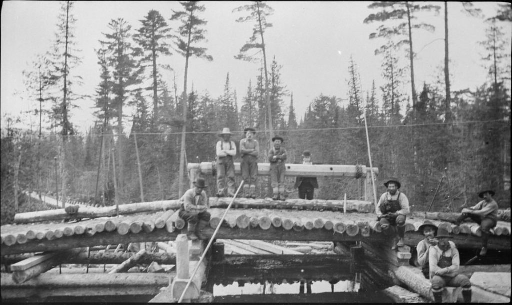 a black and white photo of nine men in overalls and shirts and hats, sitting randomly upon a wooden structure that supports a load of lumber laid in a single row; in the background stand tall trees.