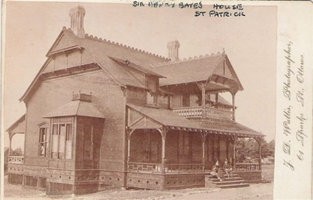 An old postcard showing a two-storey wooden house with fine details in woodwork and trim; two people sit on the front step.