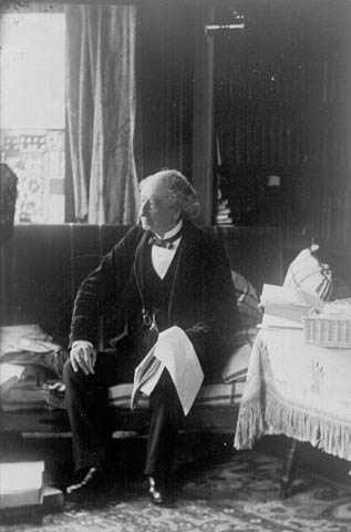 Sir John A. Macdonald in a formal suit sits upon a chesterfield holding an open sheaf of papers on his knee.
