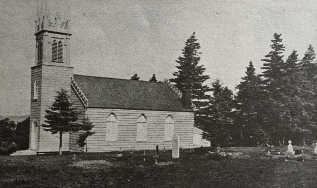A black and white image of a wooden St. Bartholomew's anglican church with a square steeple at the front, and a graveyard in the foreground.