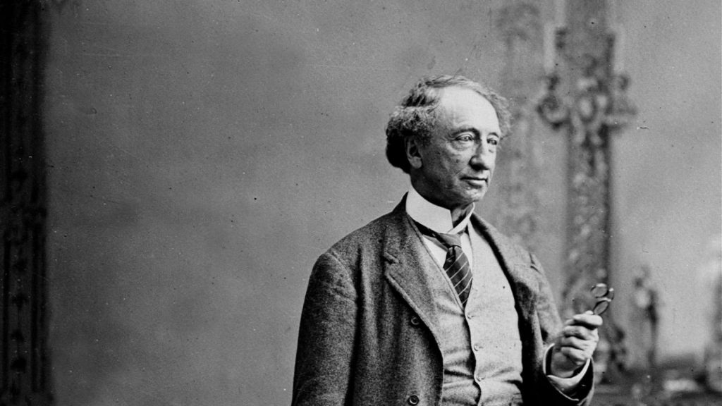 A black and white photo of Sir John A. Macdonald, an older gentleman, wearing a woolen suit holding a pair of spectacles.
