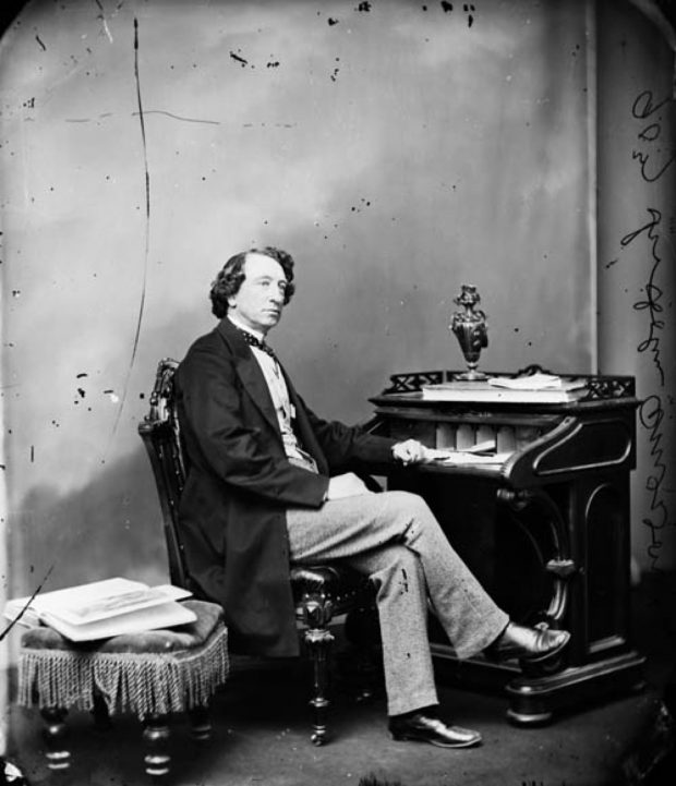 A black and white image of Sir John A. Macdonald wearing a suit, sitting at a desk, where there are books, papers and a vase.