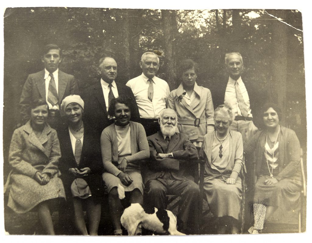 Black-and-white image of eleven people posed informally outside, with a dog in the centre.