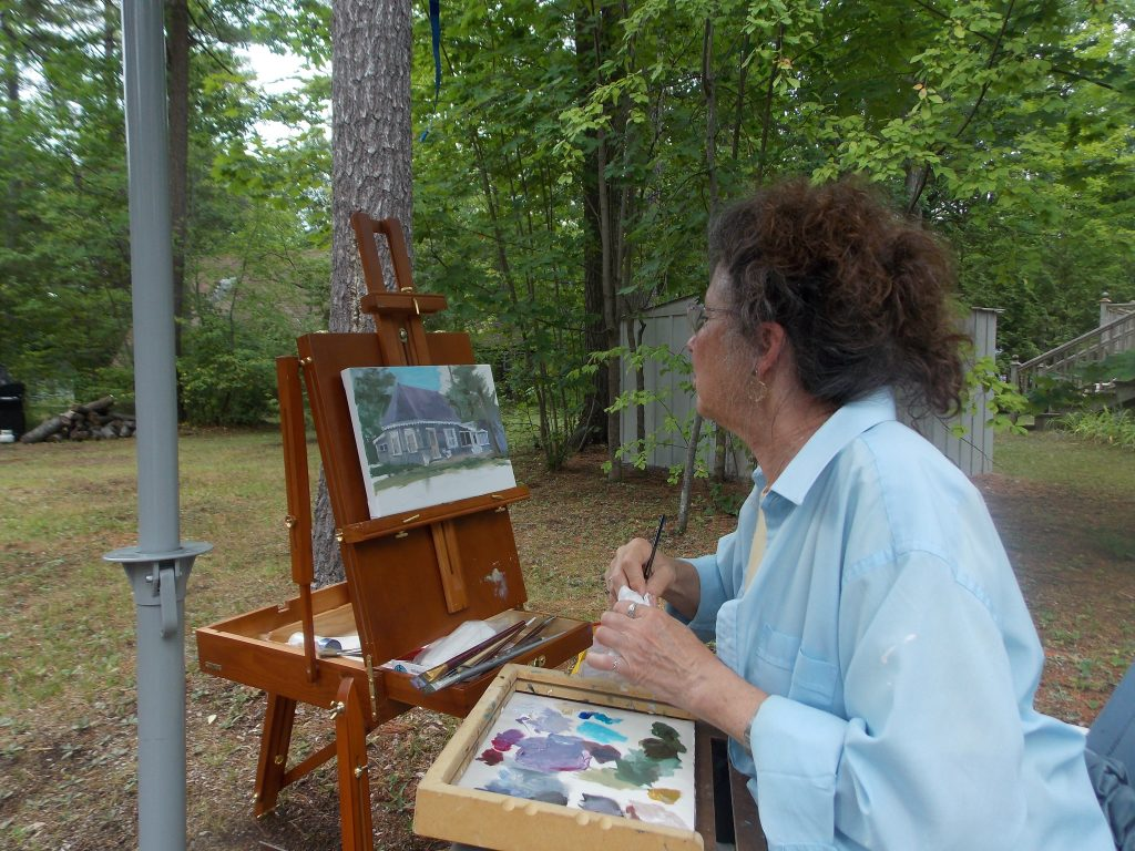 Image of someone seated outside at an easel painting a cottage.