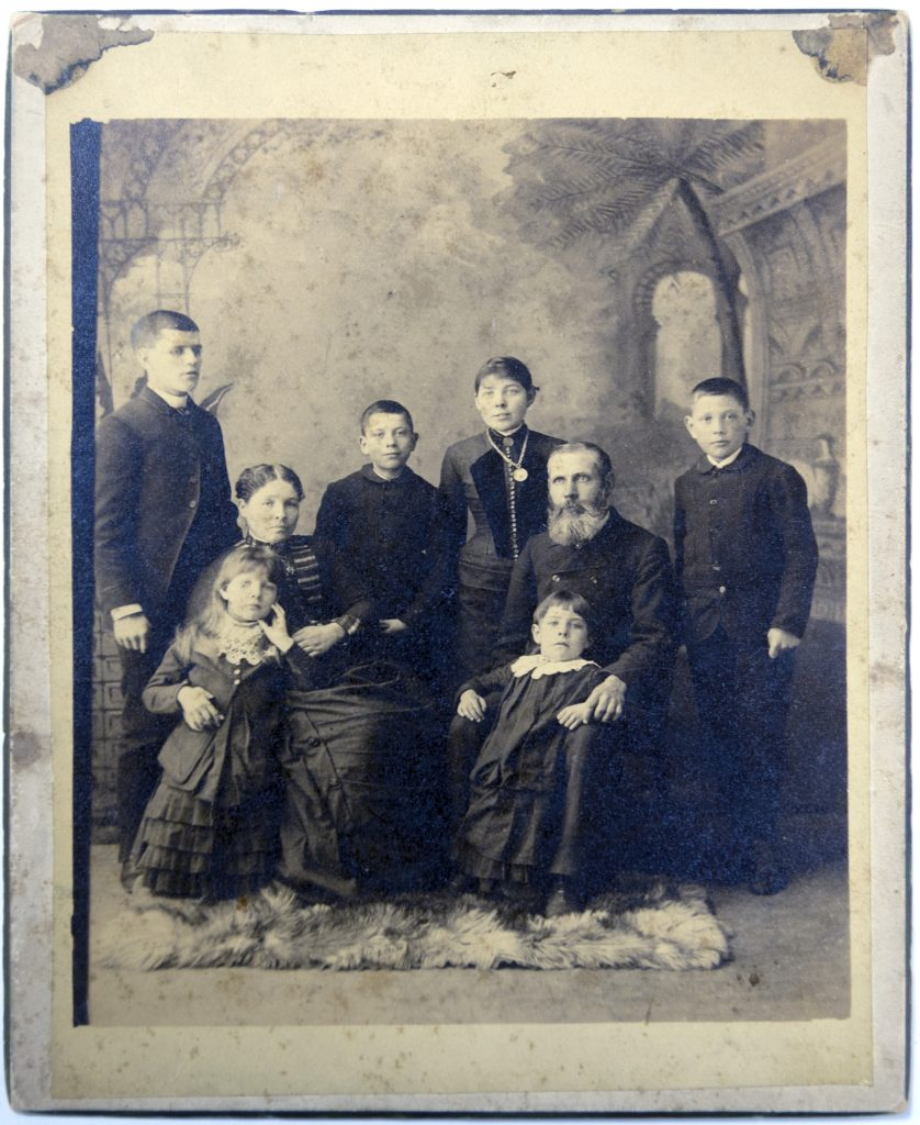 Formal portrait of seven people posed in a photography studio