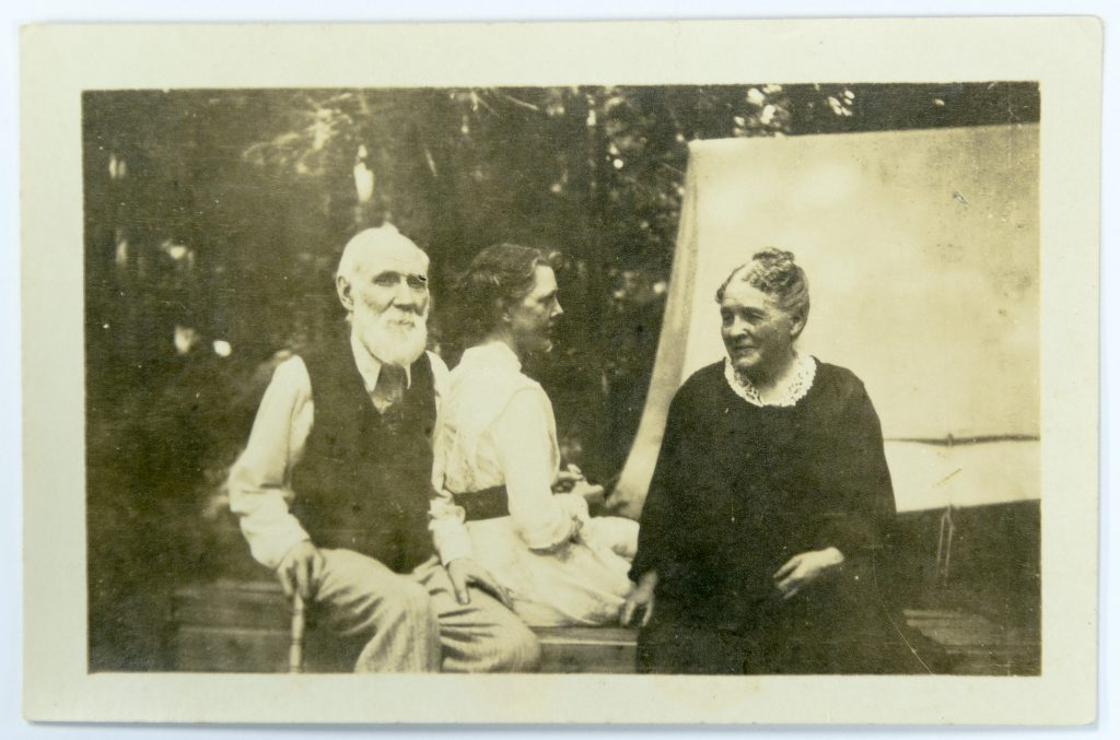 One man with beard and two women seated outside in informal attire.
