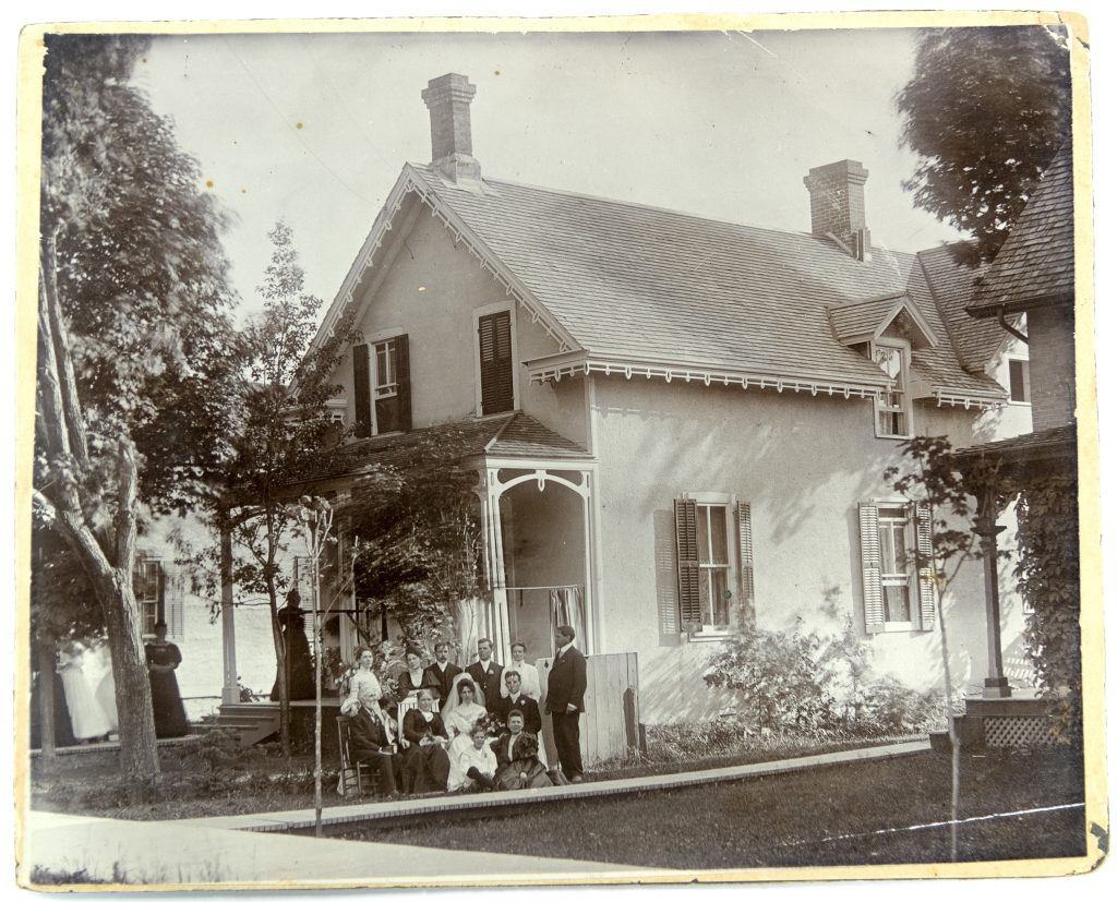Black-and-white image of a wedding party gathered beside a house.