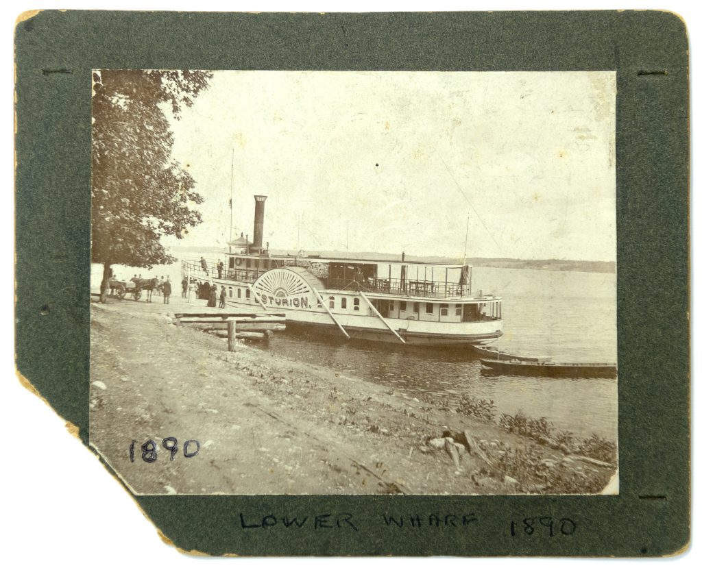 Image of large steamboat alongside dock, with people and horse-and-wagon on dock between a large tree and the boat.