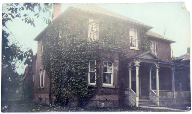 Image of large brick house covered in vines
