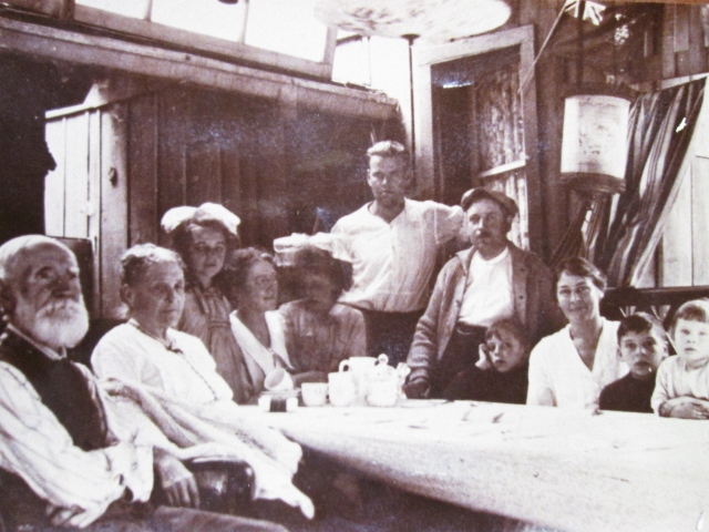 Image of black-and-white photograph showing eleven people seated around table on porch
