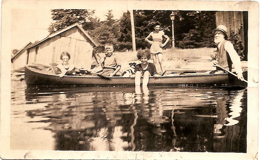 Young people in a canoe being paddled by an older man. Dock and boathouse visible in the distance.
