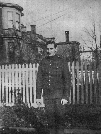 Black and white archival photograph of a man in uniform standing in front of white picket fence in front of homes, trees, and wire lines.