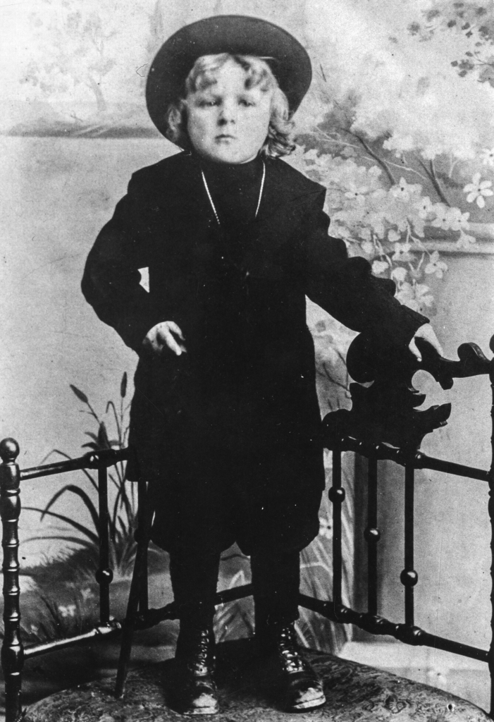 Black and white archival photograph of boy wearing dark outfit and a wide brimmed hat standing by a railing in photography studio.
