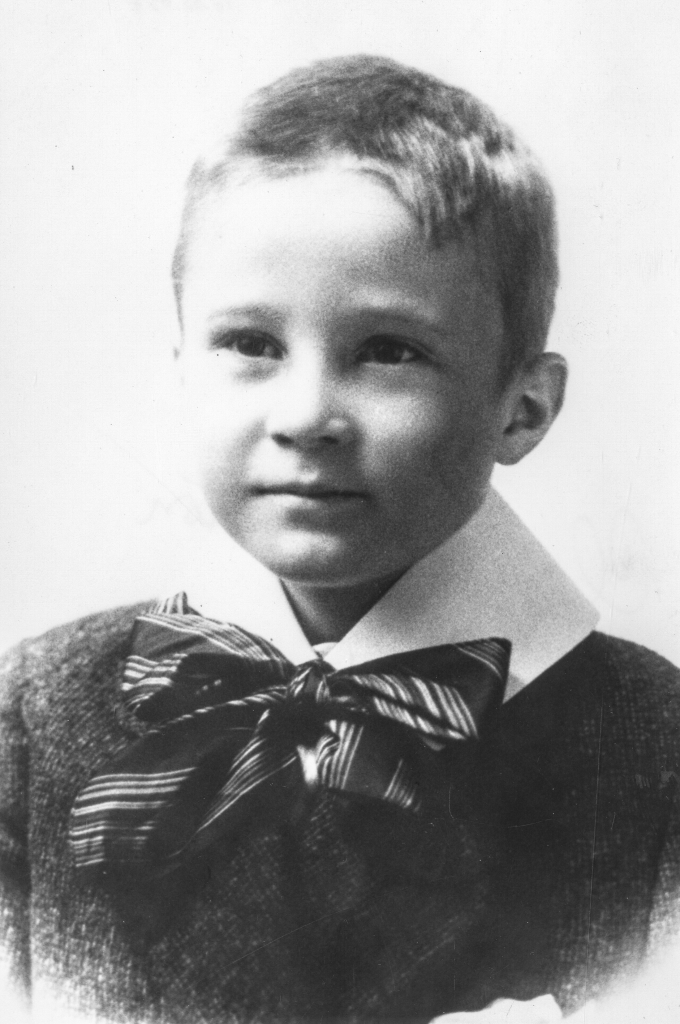 Black and white archival photograph of a boy wearing a sweater, a white collar, and a bow tie tied under his chin.