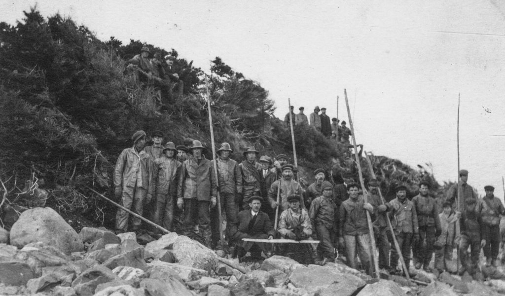 Black and white archival photograph. Group of twenty men on a beach wearing rain gear, caps, and suits holding long poles. On the hill behind the group of men are two groups of men to the left is four men sitting on the hill, and to the right is seven men standing up.