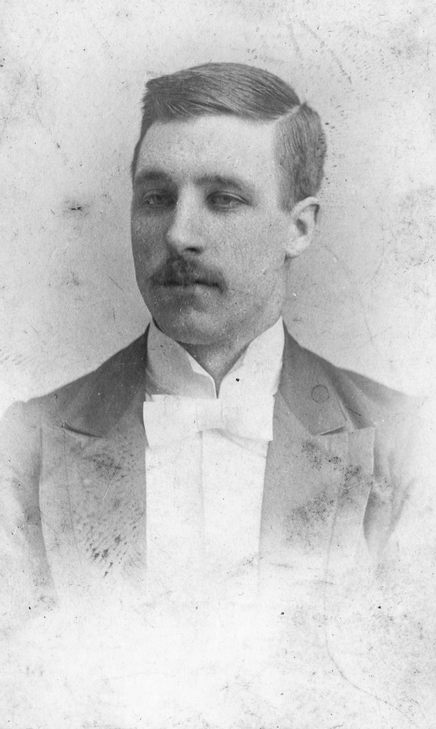 Black and white archival photograph of a man wearing suit, and bowtie.