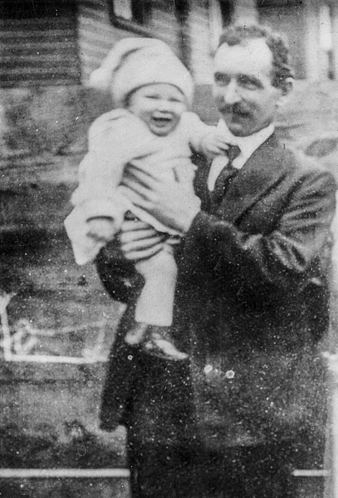 Black and white archival photograph of man standing outside of a building wearing a suit and tie and holding a baby wearing a light sweater, pants, and hat.