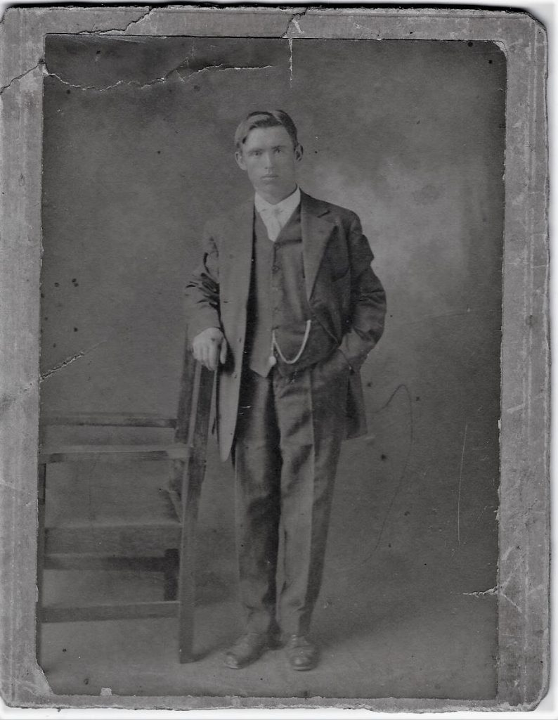 Black and white archival photograph of a man wearing a suit and tie and leaning on a chair.