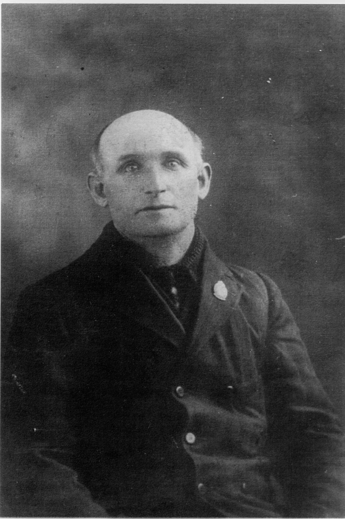 Black and white photograph of a balding man wearing an overcoat.
