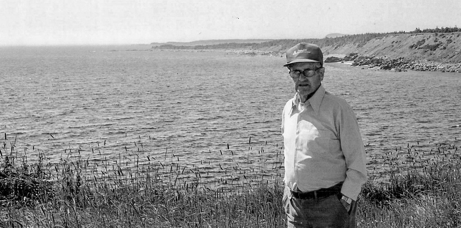 Photographie en noir et blanc d'un homme d'âge mûr portant des lunettes, une casquette de baseball, une chemise claire et des pantalons foncés. L'homme se tient dans un pré devant un paysage d'océan avec des collines à l'arrière-plan à droite.