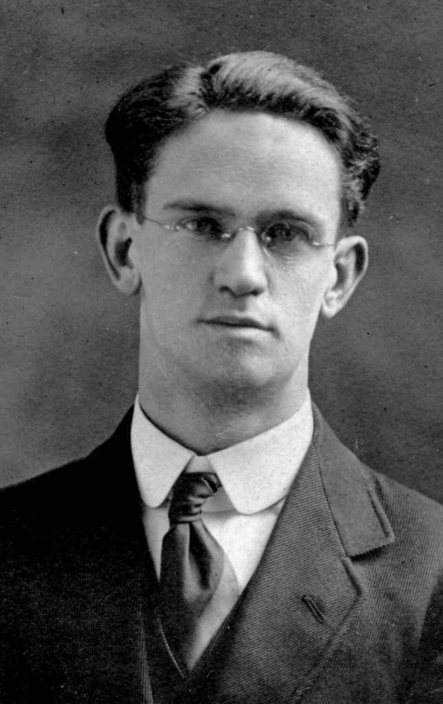 Black and white archival photograph of a man with eyeglasses wearing a suit, and tie.