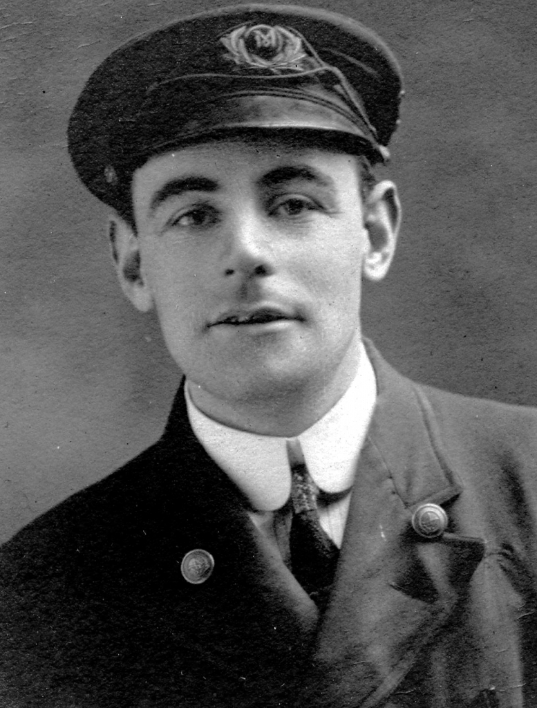 Black and white archival photograph of a man in uniform wearing a peaked cap.