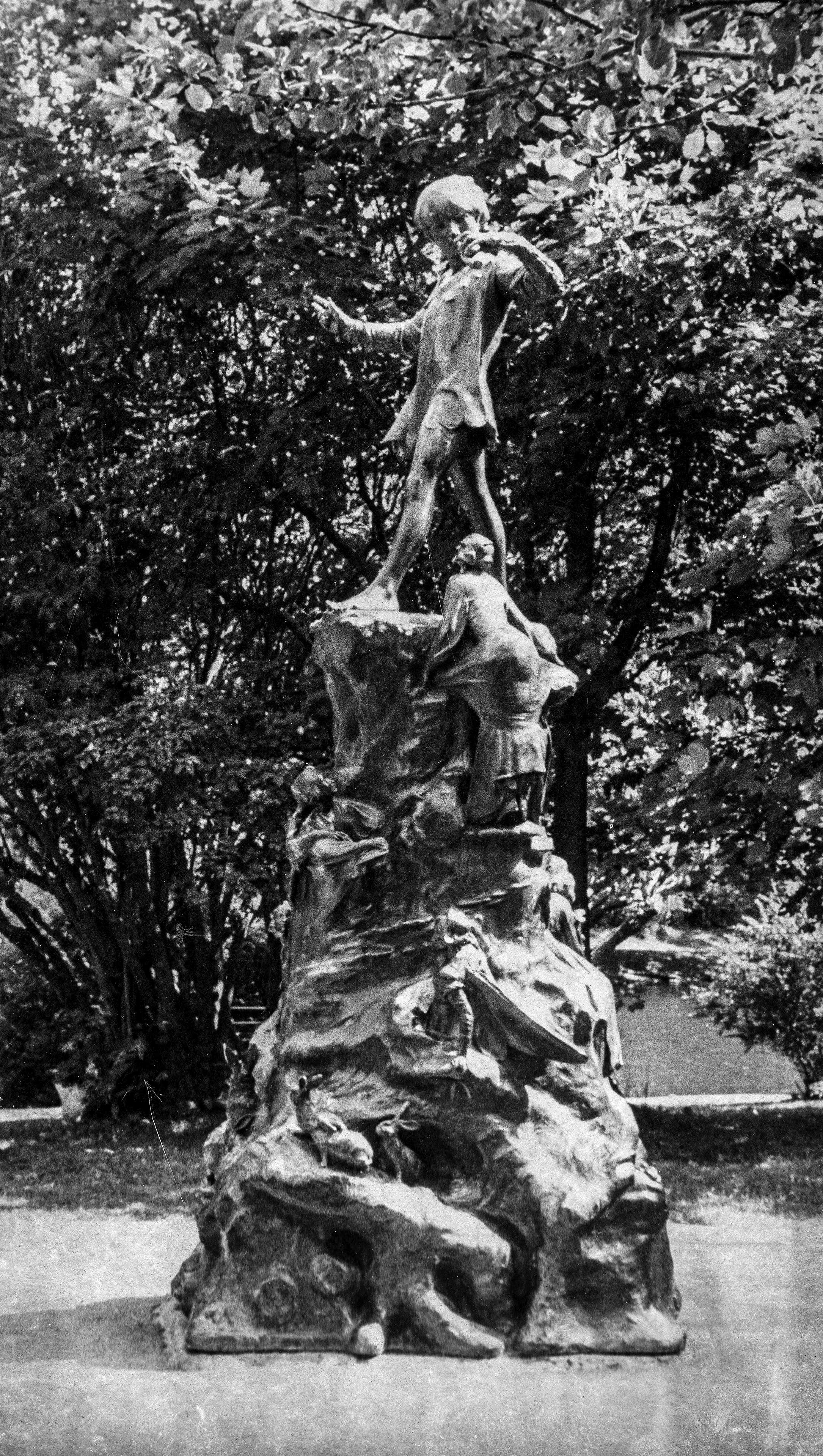 Black and white photograph of Peter Pan Statue. Tall statue with animals, people, and a boy standing on top.