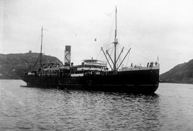 Black and white archival photograph. Large passenger liner ship, the SS Florizel, in the St. John's harbour. Behind ship to the left is a hill with a stone tower on it, and to the right are hills. People can be seen on the ship deck.