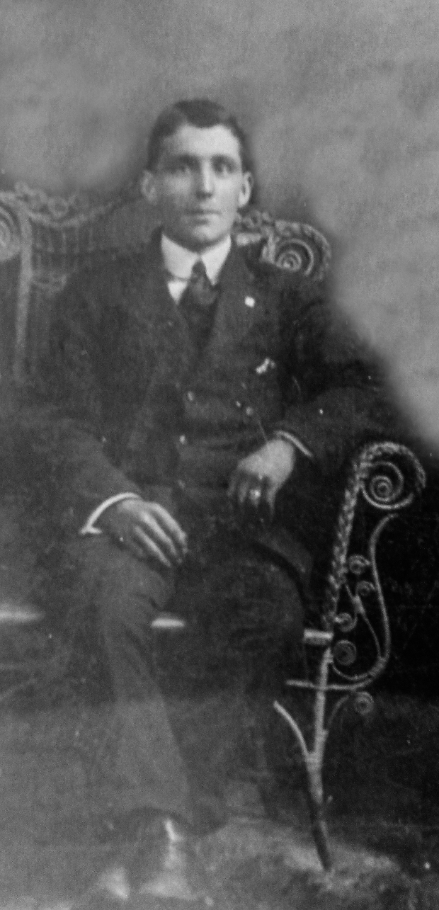 Black and white archival photograph of man sitting in a chair wearing a suit and tie.