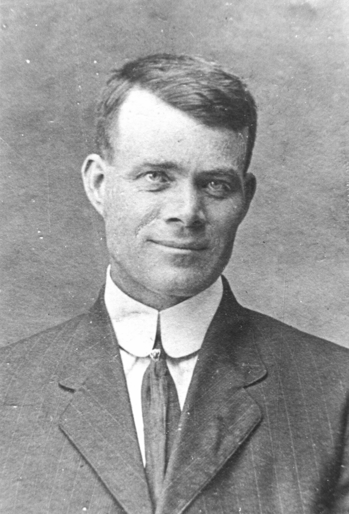 Black and white archival photograph of a man wearing a suit, and tie.