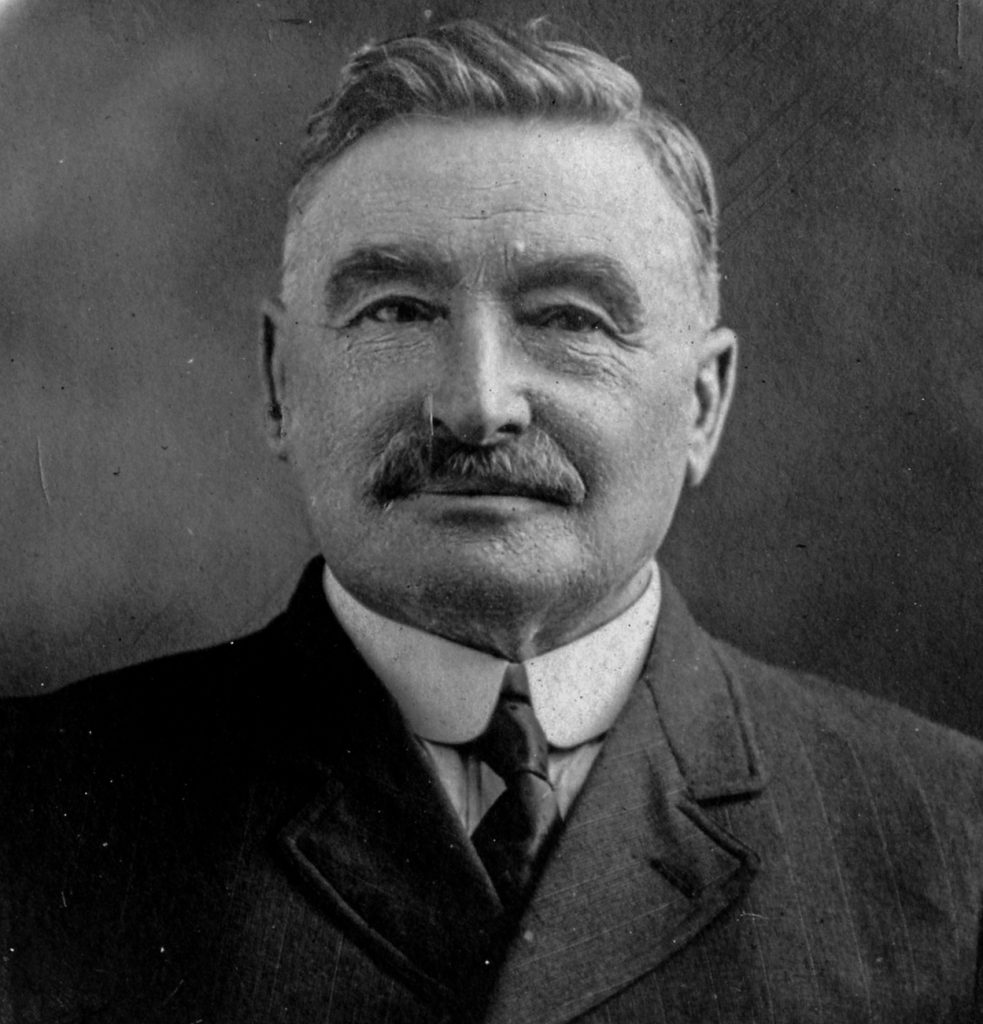 Black and white archival photograph of a man with a moustache wearing a suit and tie.