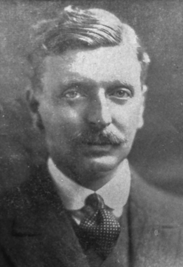 Black and white archival photograph of a man with a moustache wearing a suit, and tie.