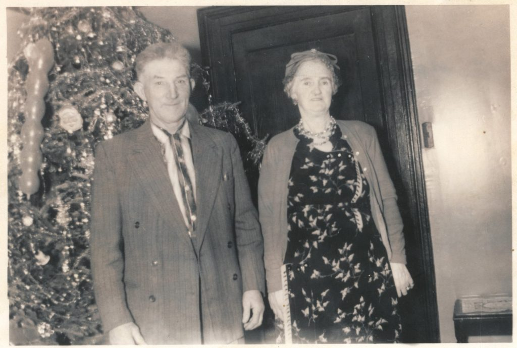 Black and white archival photograph of a man in a suit, and a woman in a dress, cardigan, hat, and necklace standing in front of Christmas tree covered in tinsel and ornaments.