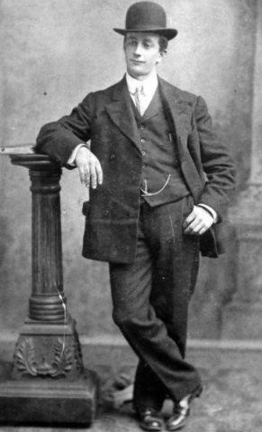 Black and white archival photograph of man leaning against post while wearing a suit, tie, and bowler hat.