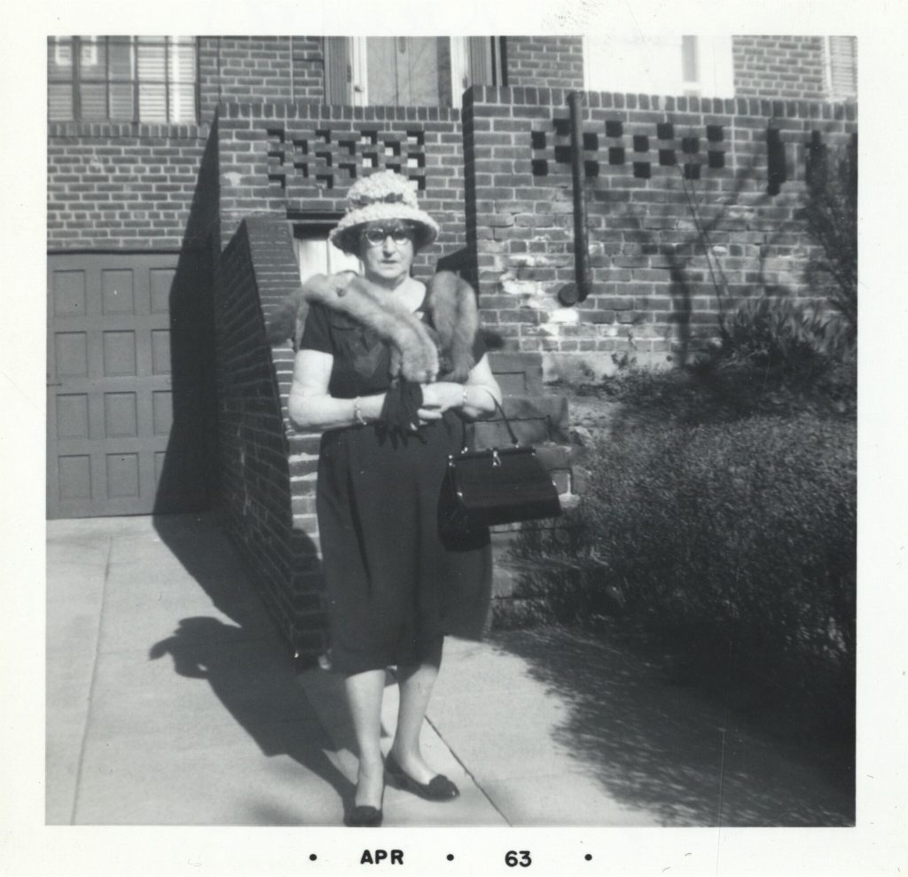 Black and white archival photograph of a woman in a dress, fur collar, hat, and glasses carrying gloves and a purse standing outside in front of a brick building.