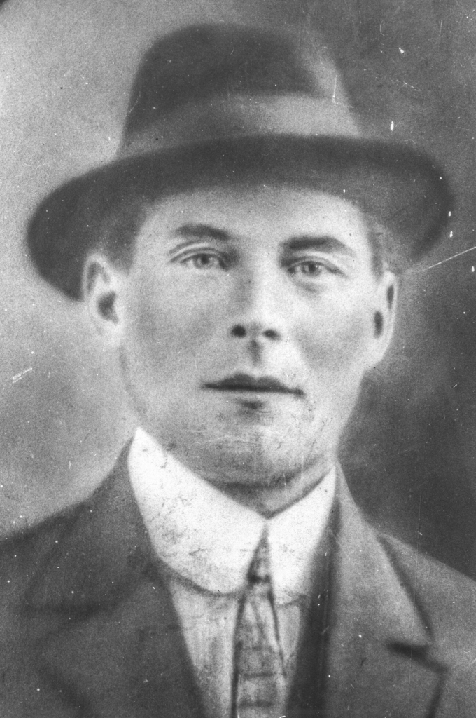 Black and white archival photograph of a man wearing a fedora hat, suit, and tie.