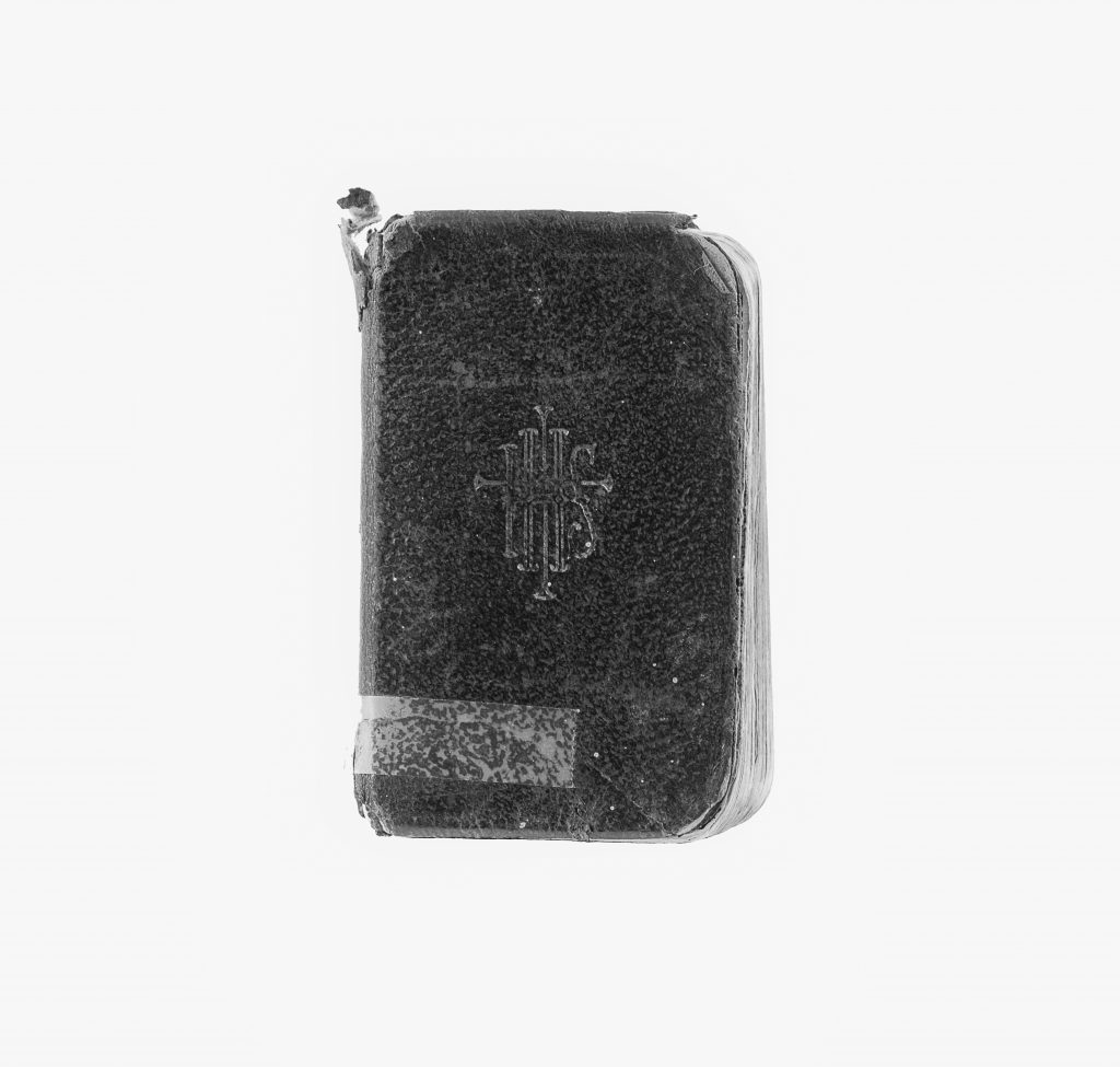 Black and white modern photograph of prayer book with black cover and white pages. Cover has IHS inscribed on the front.