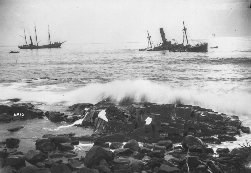 Black and white archival photograph of large passenger liner ship, the SS Florizel, run aground in the ocean just offshore from rocky beach. Seven rescue boats can be seen around the Florizel. Large rescue ship can be seen to the left of Florizel with two smaller rescue boats to the left of large ship.